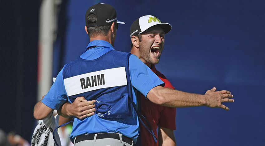 Jon Rahm and caddie celebrate eagle at 18