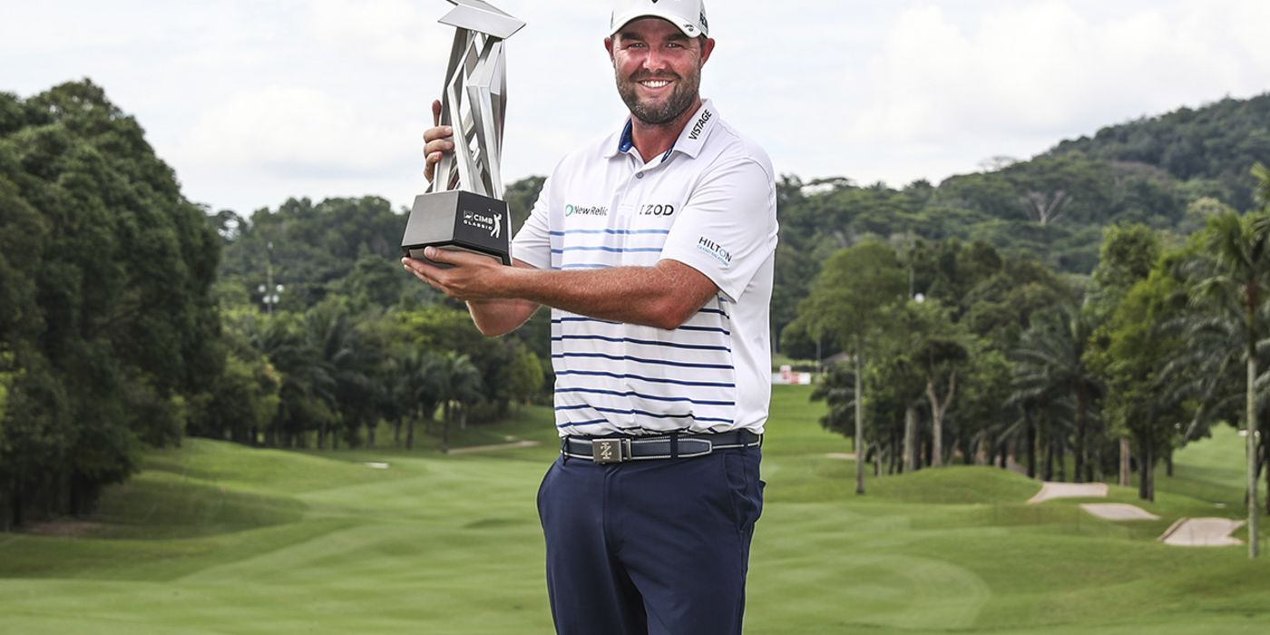 Marc Leishman hoists the CIMB trophy