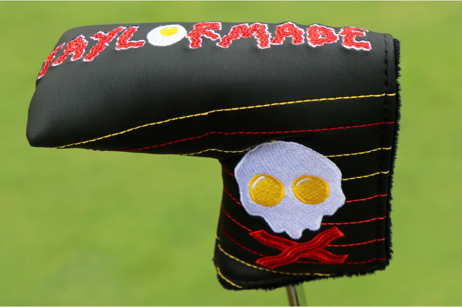 Collin Morikawa's new TaylorMade putter cover, where Skull and crossbones meets bacon and eggs. Morikawa loves his breakfast, as his breakfast-stamped Titleist Vokey SM7 wedges showcase.